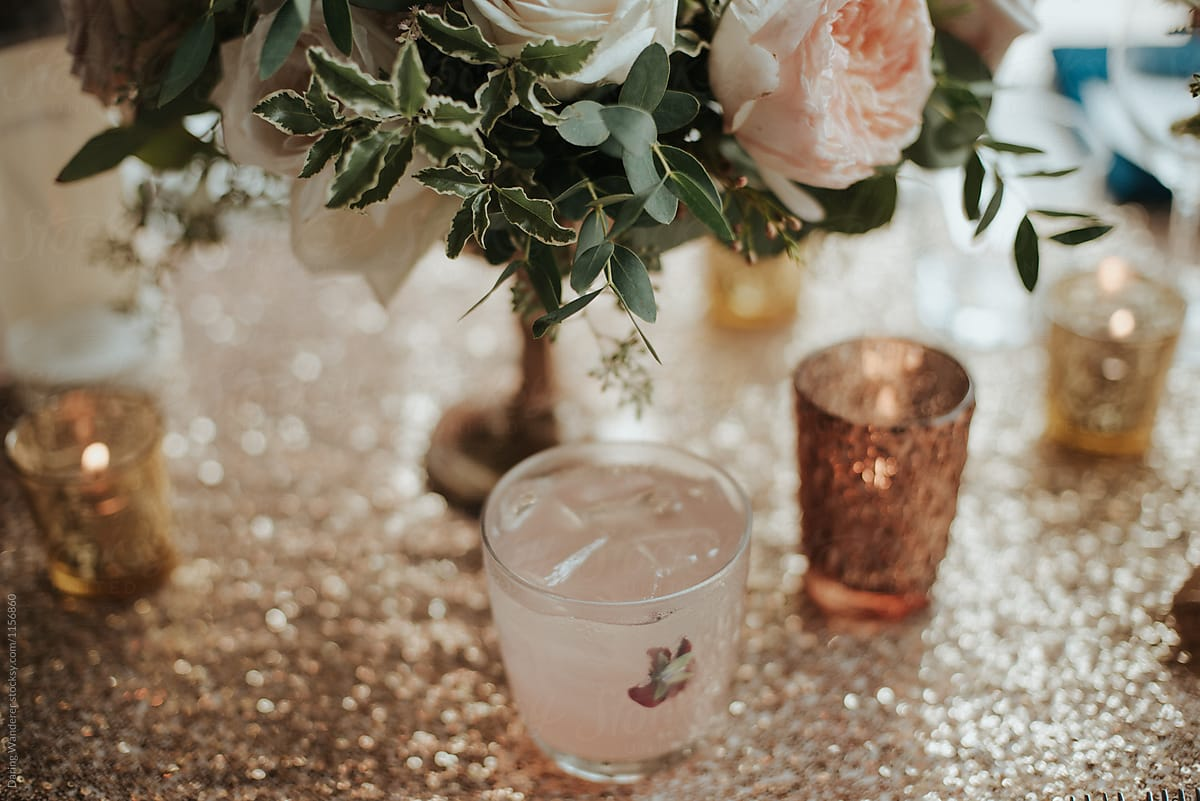Pink lemonade cocktail drinks on sequin table with elegant floral pink lemonade cocktail drinks on sequin table with elegant floral arrangement by daring wanderer for stocksy mightylinksfo