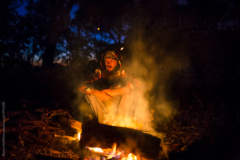 A man sits and reflects by the campfire by Reece McMillan for Stocksy United