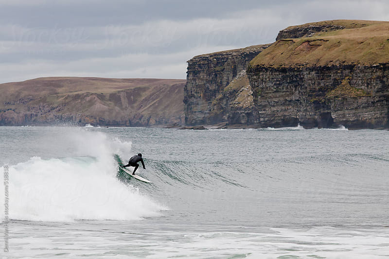 Surfer surfing a wave surrounded by cliffs. by Denni Van Huis for Stocksy United