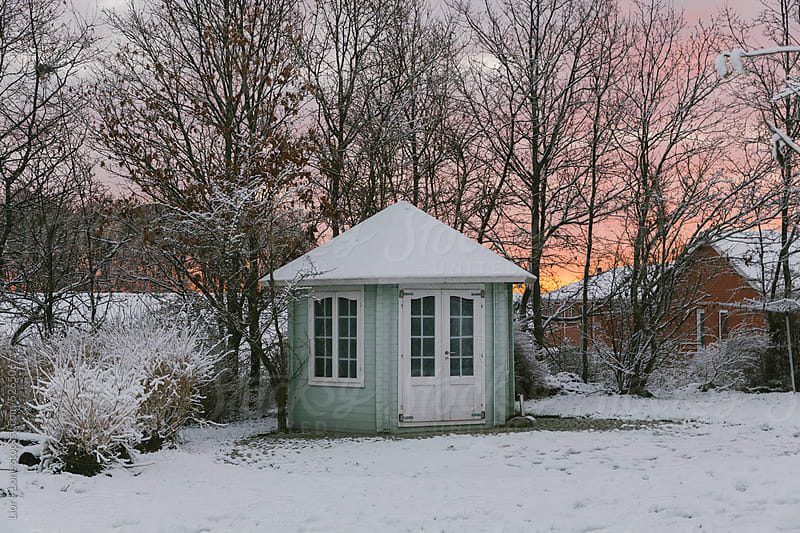 Small wooden pavillion in snow landscape at sunrise by Lior + Lone for Stocksy United