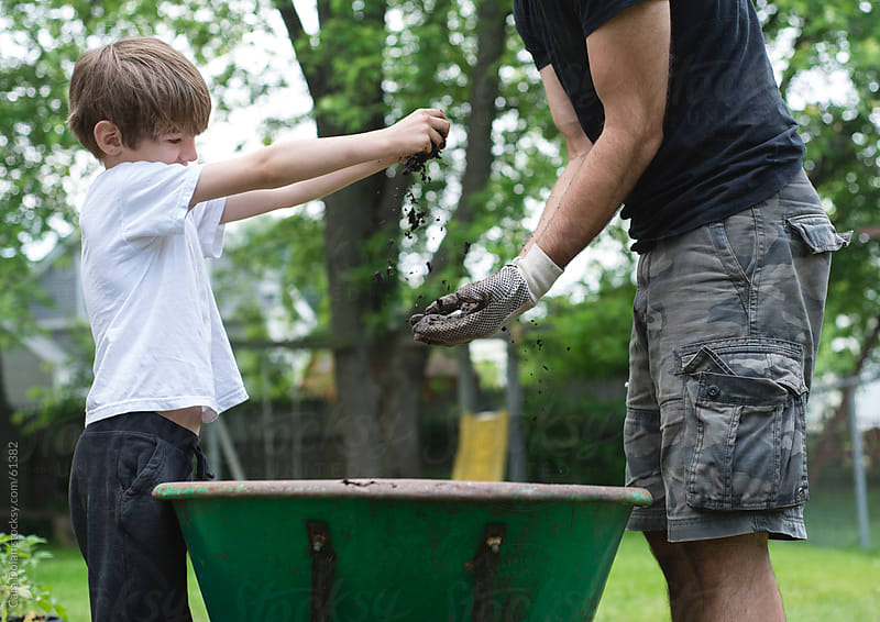 Boy and his dad play with dirt from the garden  by Cara Dolan for Stocksy United