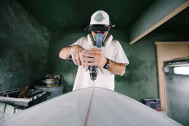 Shaper drilling hole into surfboard for leash plug installation by Urs Siedentop & Co for Stocksy United