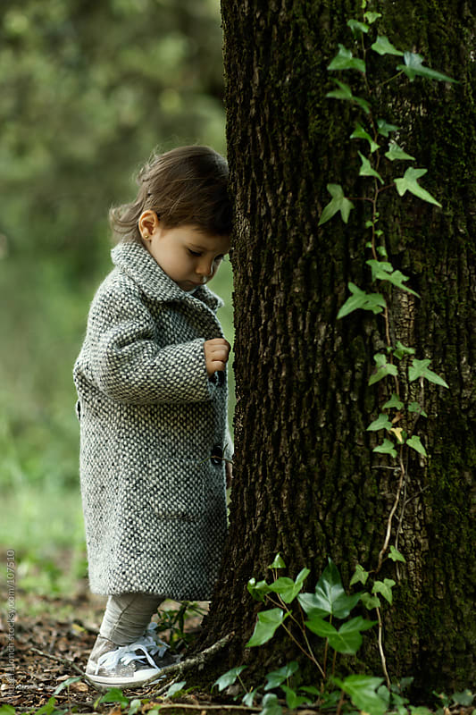 Little girl with coat and big tree by Miquel Llonch for Stocksy United