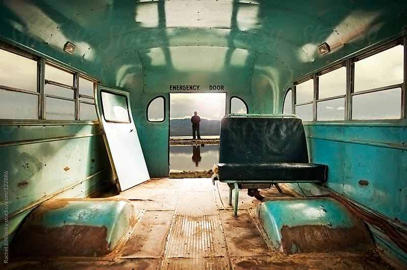 A man in a distant watery horizon seen through the emergency exit of a rusty abandoned bus by Rachel Bellinsky for Stocksy United
