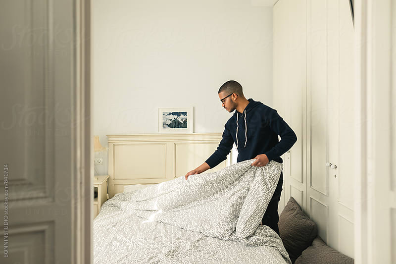 Latin man making bed at home. by BONNINSTUDIO for Stocksy United