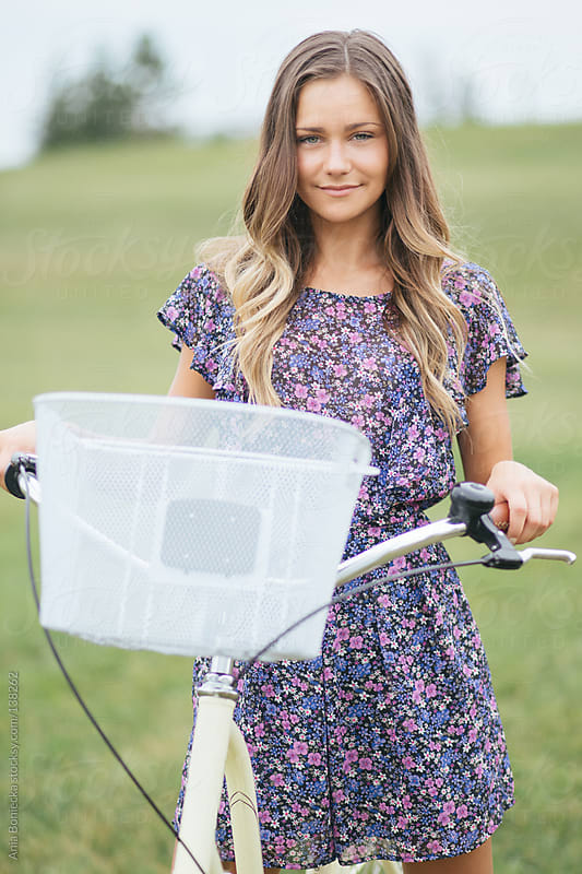 A young girl holding her bike smiling at the camera by Ania Boniecka for Stocksy United