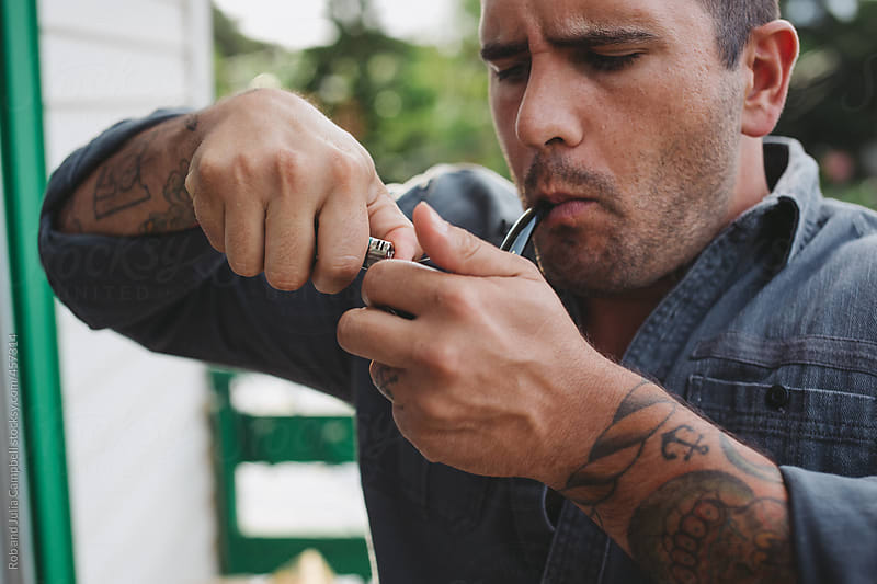 young man lighting pipe by Rob and Julia Campbell for Stocksy United