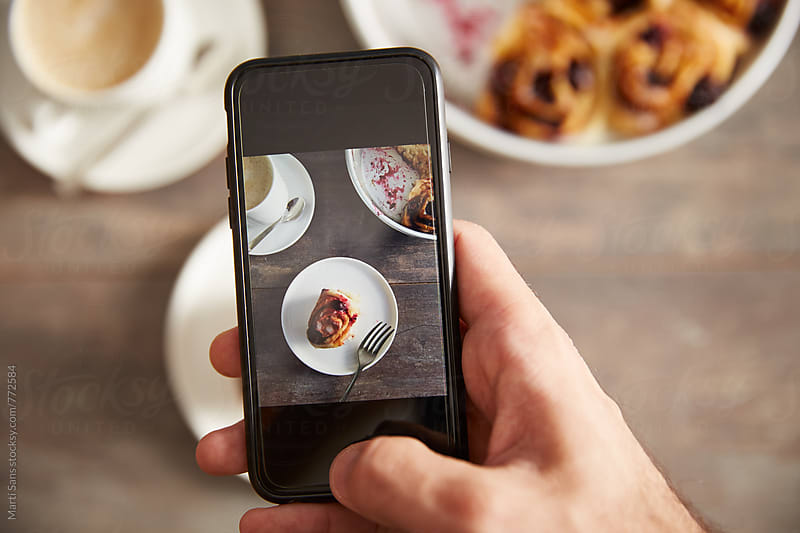 Smartphone taking picture of blueberry roll by Martí Sans for Stocksy United