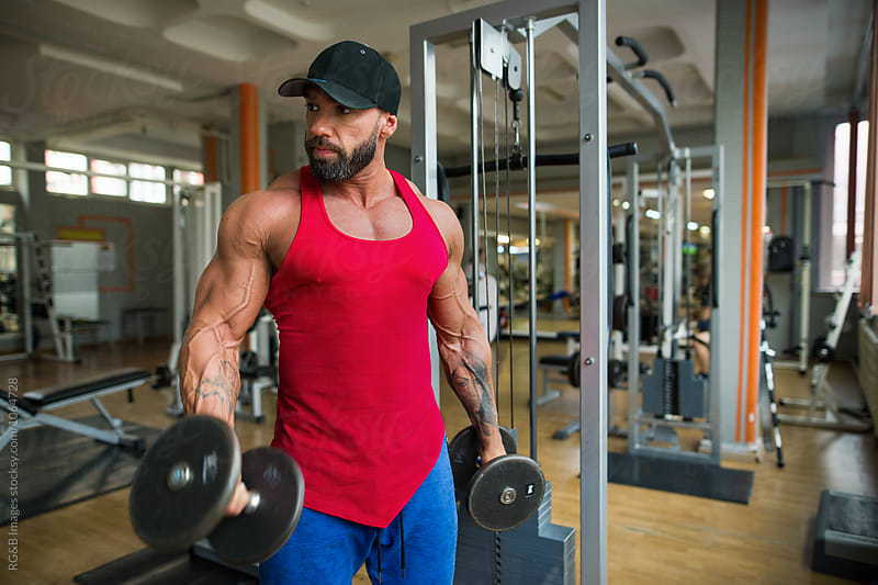 Mulcular man doing weight training at the gym by RG&B Images for Stocksy United
