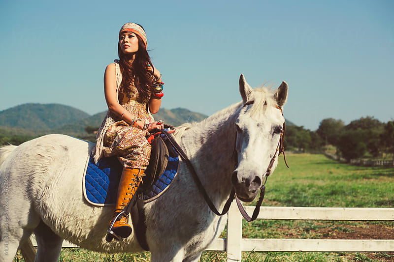 Asian Hippie Woman Riding a Horse by Marija Savic for Stocksy United