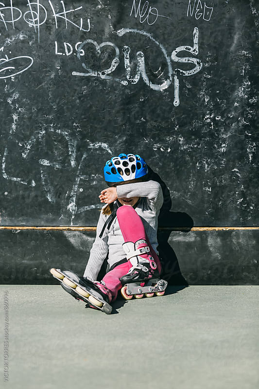 Little Girl Resting After Roller Skating in the Rink by VICTOR TORRES for Stocksy United