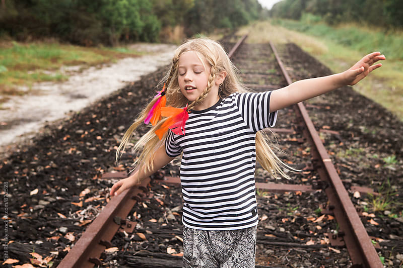 girl spinning around on old train tracks  by Tahl Rinsky for Stocksy United