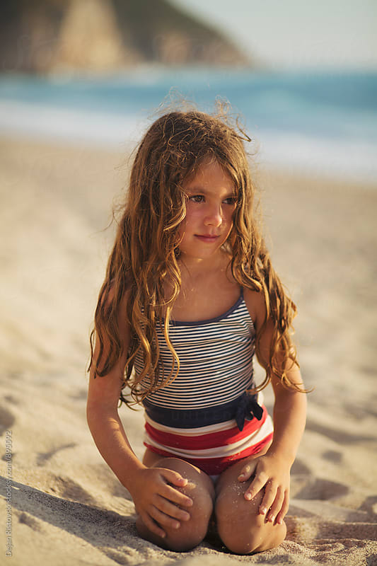 Little girl sitting in the sand. by Dejan Ristovski for Stocksy United