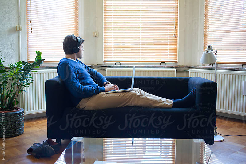 Young man looking away while sitting on the couch with a laptop and headphones by Ivo de Bruijn for Stocksy United