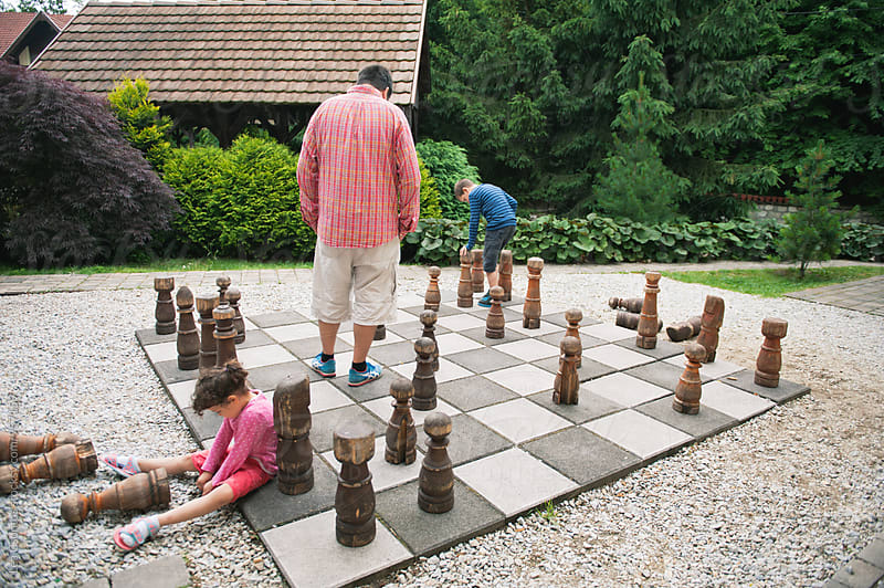 Family playing chess on a giant outdoor board by Lea Csontos for Stocksy United