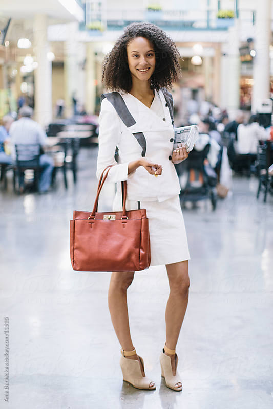 A business woman smiling holding a bag and a newpaper by Ania Boniecka for Stocksy United