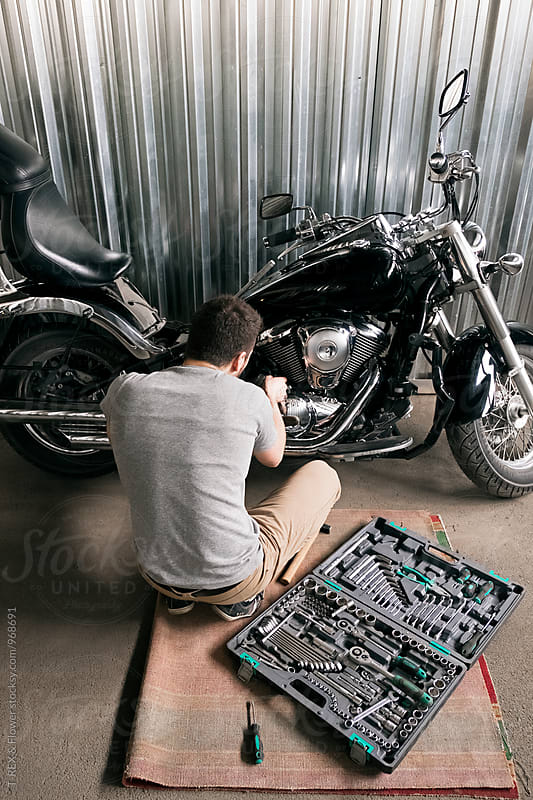Back view of man reparing motorcycle by T-REX & Flower for Stocksy United