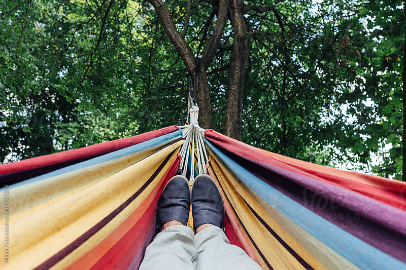 Man in blue sneakers lying in colorful hammock, top view, personal perspective, footsie. by Mima Foto for Stocksy United