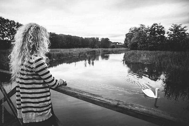 Young woman looking a swan on the river by michela ravasio for Stocksy United