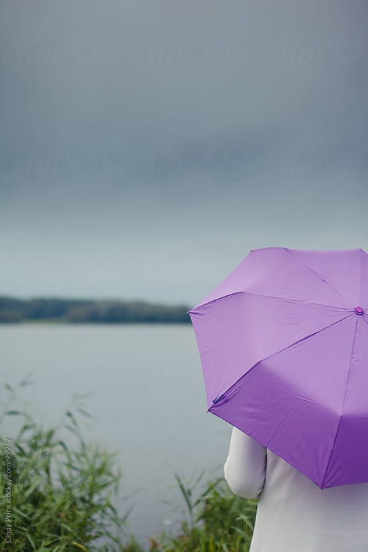Woman holding a purple umbrella in the rain overlooking a lake by Cindy Prins for Stocksy United