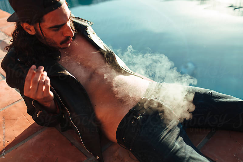 A young male sits poolside smoking a cigarette  by HOWL for Stocksy United