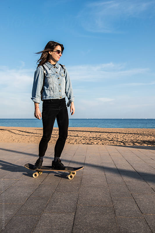 Young woman skating on the beach, Barcelona by Bisual Studio for Stocksy United