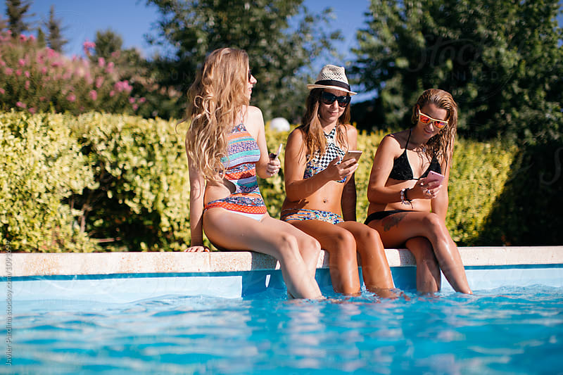 women enjoy in the pool by Javier Pardina for Stocksy United