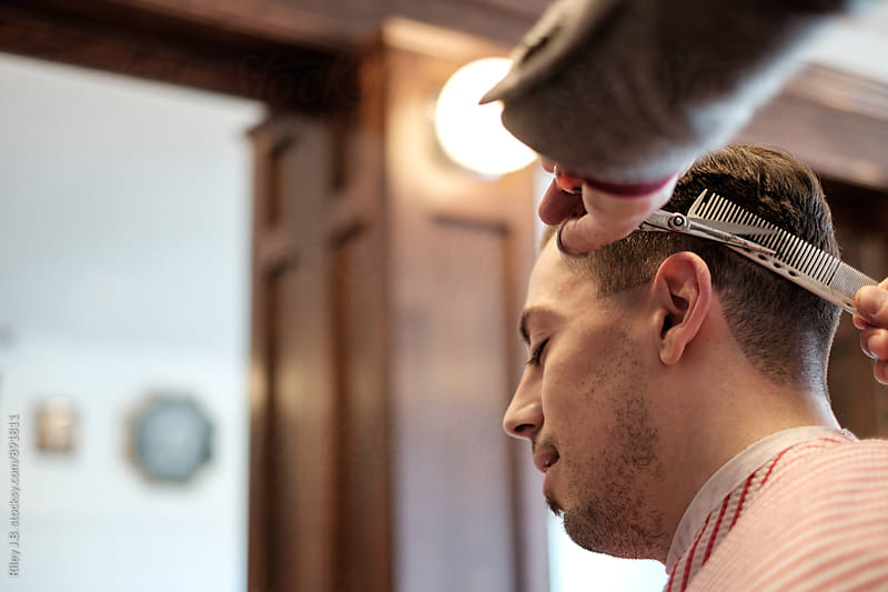 A barber uses a comb & scissors to cut a clients hair. by Riley J.B. for Stocksy United