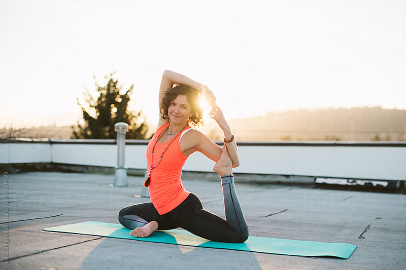 Young woman doing a seated yoga pose at sunset. by Kate Daigneault for Stocksy United