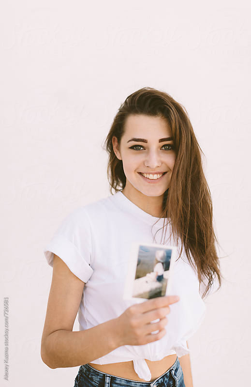 Young woman holding instant photo with her by Alexey Kuzma for Stocksy United