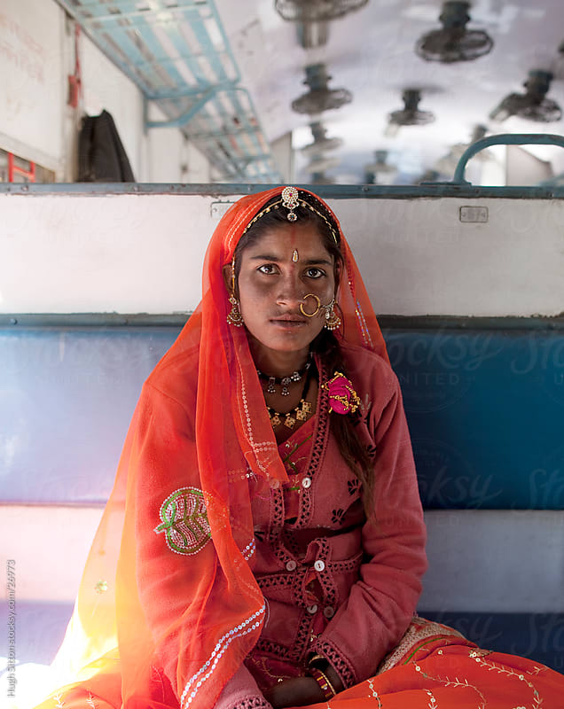 Portrait of Rajasthani woman sitting on train.  by Hugh Sitton for Stocksy United