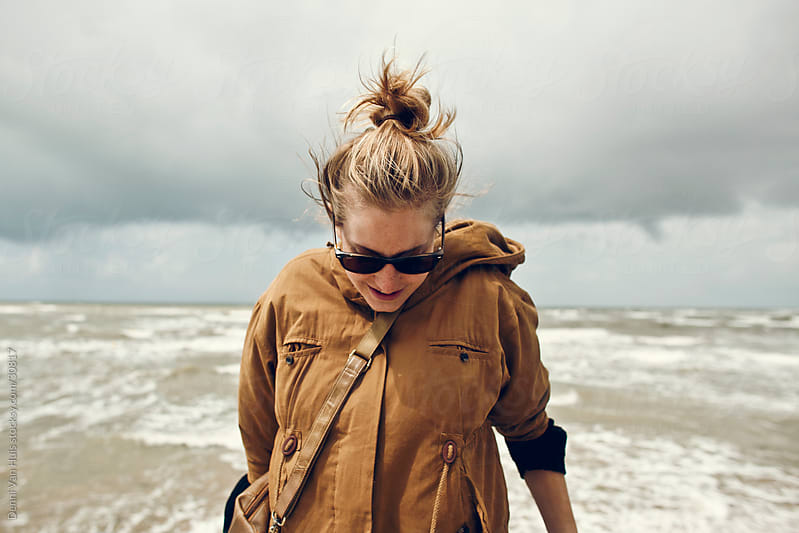 Young woman enjoying the storm that is coming on the beach by Denni Van Huis for Stocksy United