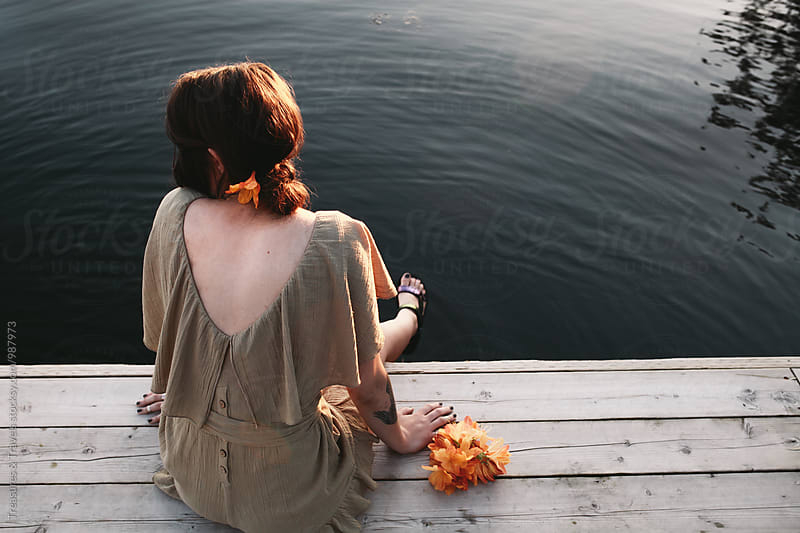 Young woman sitting on pier by Treasures & Travels for Stocksy United