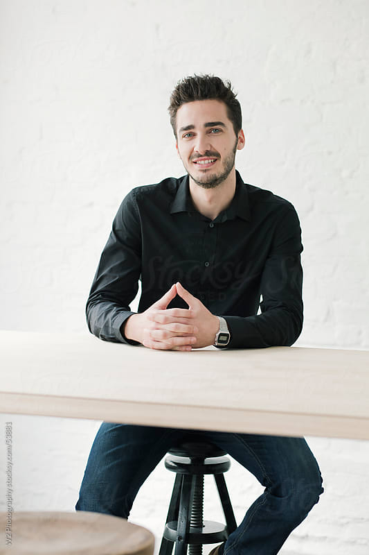 Portrait of smiling young executive at a desk. by W2 Photography for Stocksy United