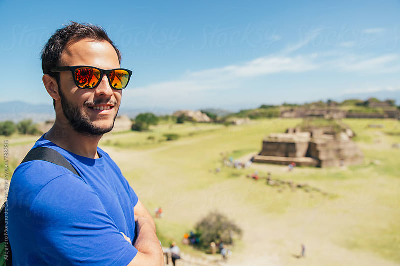 Young man tourist posing in front of some ancient ruins landmark in Mexico by Alejandro Moreno de Carlos for Stocksy United
