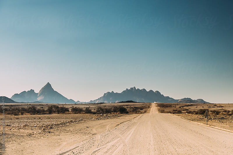 long empty road in a desert by Micky Wiswedel for Stocksy United