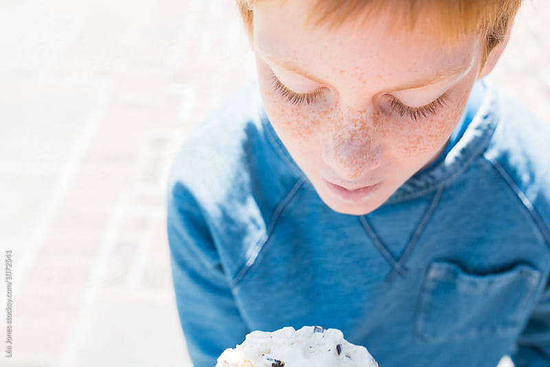 redhead boy with freckles eating ice cream by Léa Jones for Stocksy United