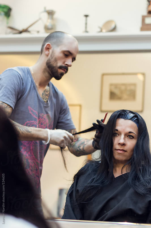 Woman is getting her hair colored by a  tattooed hairdresser by Leander Nardin for Stocksy United