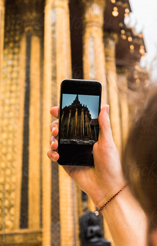 Man taking photo of Golden Temple in Grand Palace /Bangkok with his smartphone. by Audrey Shtecinjo for Stocksy United