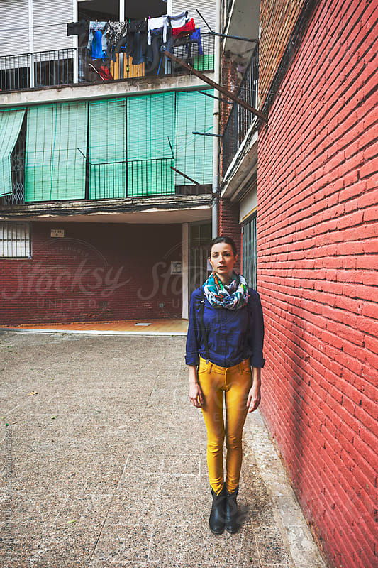 Beautiful woman standing next to red brick wall. by BONNINSTUDIO for Stocksy United