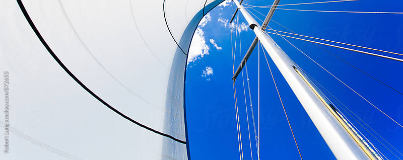 White sails on a blue sky day by Robert Lang for Stocksy United