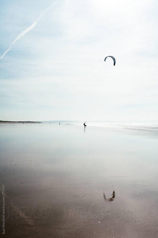 Man kiteboarding at the beach by Suzi Marshall for Stocksy United