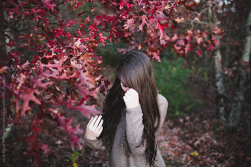 Girl in fall leaves by Joe St.Pierre Photography for Stocksy United