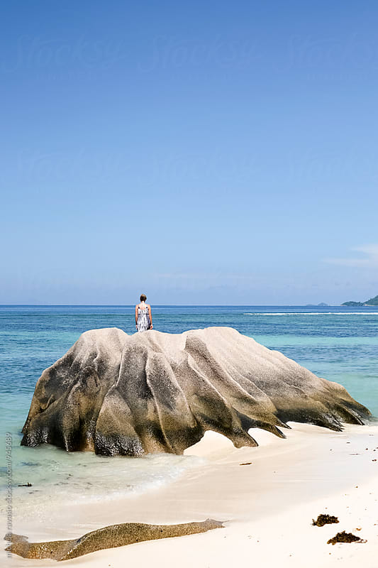 Woman standing on a granite rock on the beach by michela ravasio for Stocksy United