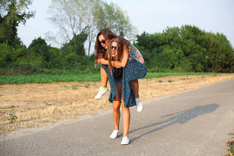 Two beautiful stylish female friends having fun outdoors by Marija Mandic for Stocksy United