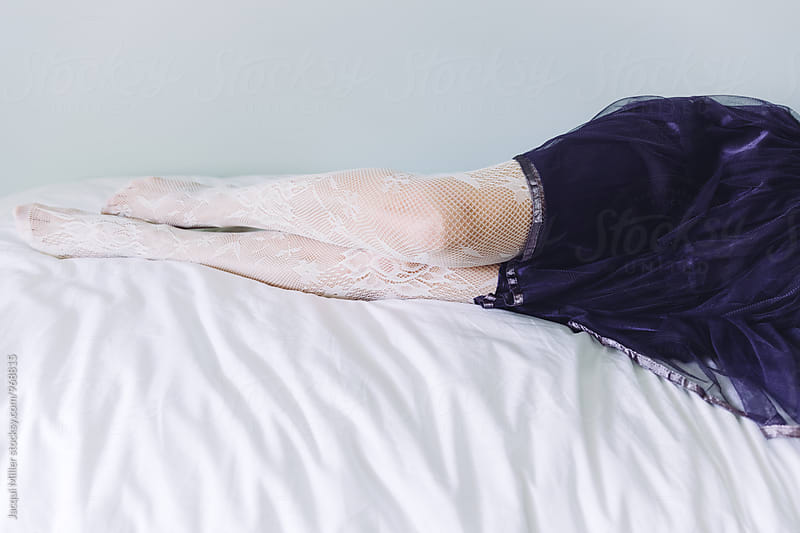 Legs of woman wearing purple tulle skirt and tights, resting on a bed by Jacqui Miller for Stocksy United