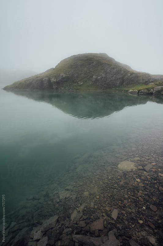 Mountain lake in fog by Peter Wey for Stocksy United
