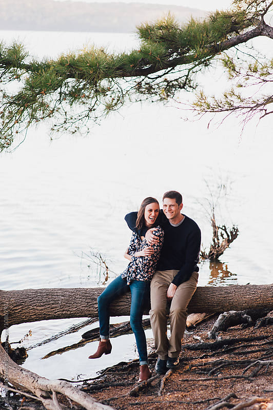 Couple Sitting on a Fallen Log on the Lake Shore by michelle edmonds for Stocksy United