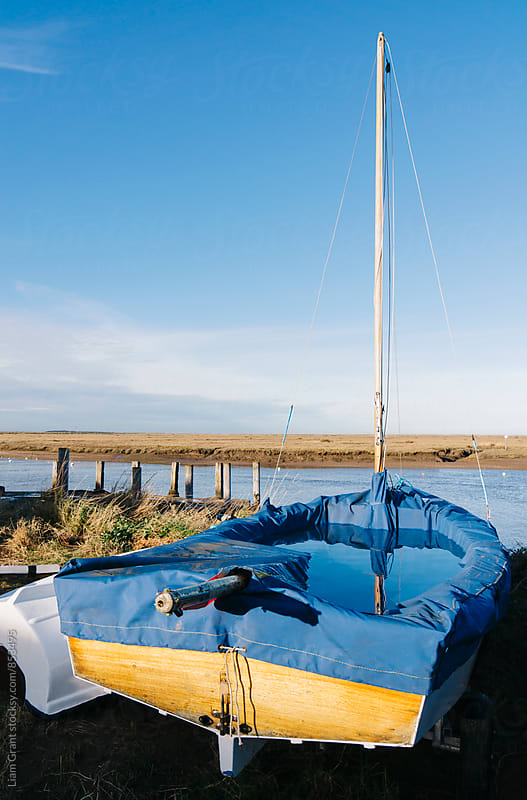 Covered sailing boat at Burnham Overy Staithe, Norfolk, UK. by Liam Grant for Stocksy United
