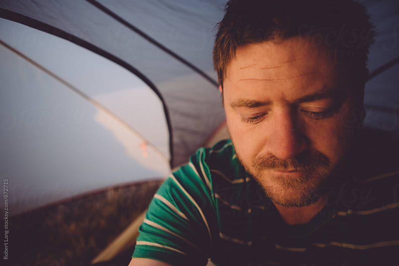 Waking up early in a tent while camping by Robert Lang for Stocksy United